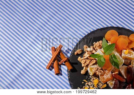Top view of nutritious confectionery ingredients on a plate on a striped fabric background. Light brown walnuts, fresh peppermint and cinnamon with turkish delight in a sugar powder. Copy space.