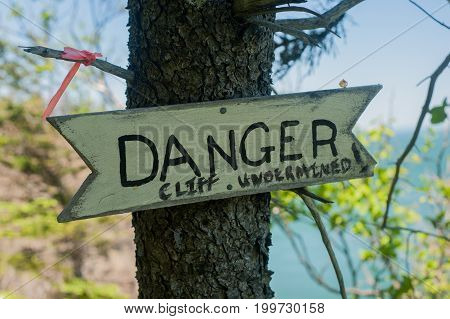 danger sign in the woods on a tree