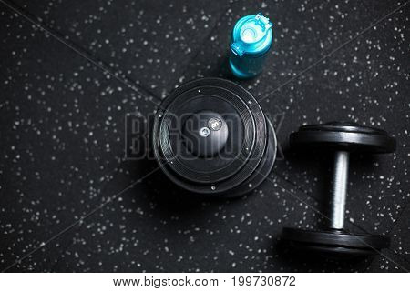 Top view of a blue plastic bottle for water and two heavy dumbbells, stuff for weight sports competitions, routines and workouts on a dark blurred background.