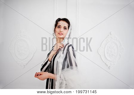 Portrait Of Bride Posing With Her Long Veil In The Big White Room.