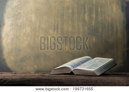 Bible and a crucifix on a old table. Beautiful gold background.Religion concept.