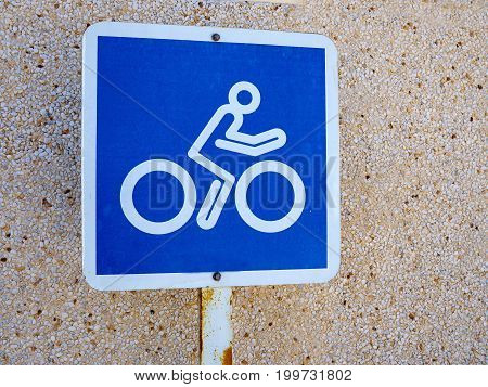 Bicycle lane blue and white sign by a wall