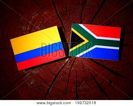 Colombian Flag With South African Flag On A Tree Stump Isolated