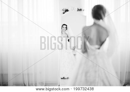 Pretty Bride In Outstanding Wedding Dress Looking In The Mirror In Big White Room. Black And White P