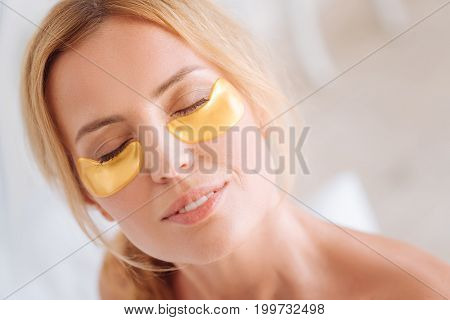 Gel patches. Enigmatical young woman keeping smile on her face and closing eyes while being deep in thoughts