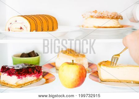fridge filled with cake, sweets and an apple. however, it looks like this guy is going for the unhealthy alternative. again.