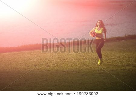Runner and success. Girl sunny outdoor with fitness mat. Coach or trainer at workout. Sport and sportswear fashion. Woman running on green grass.