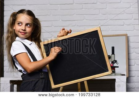 Schoolgirl With Cunning Face Holds Small Blackboard