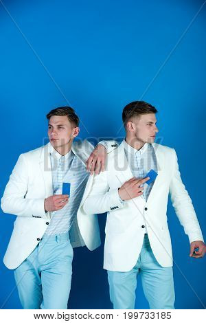 Men holding blank cards on blue background. Business communication and meeting. Banking and saving concept. Businessmen wearing white jackets. Cooperation and partnership.