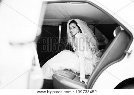 Flawless Bride Sitting In Wedding Car. Black And White Photo.