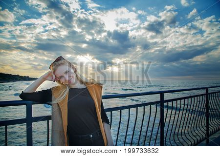 happy blond woman standing at evening sea coast under light rays