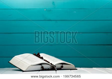 Bible and the crucifix on a white wooden table. Beautiful aquamarine wood background. Religion concept