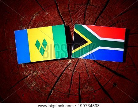 Saint Vincent And The Grenadines Flag With South African Flag On A Tree Stump Isolated