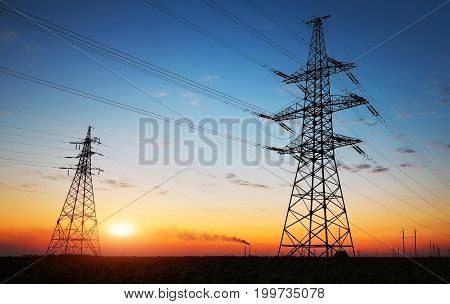 Silhouette of electricity pylons and high-voltage power lines on the field at sunset. Wire electrical energy at sunrise
