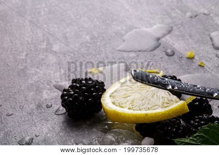 A gray table with sappy blackberries, drops of water, yellow slice of lemon, fresh green leaves of mint and a metallic moist spoon on a gray blurred background.