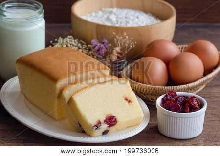 Slices of butter cake on white plate. Homemade butter cake with dried cranberries so delicious soft and moist. Tasty pound cake or butter cake served on wood table. Homemade bakery background concept. Delicious butter cake ready to served.