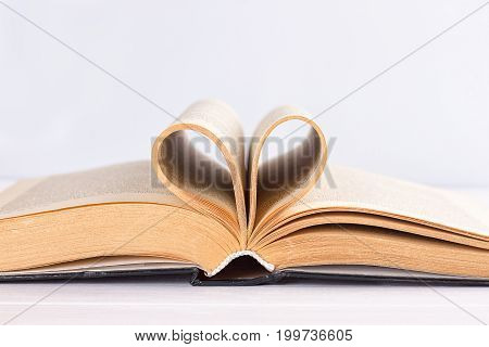 Pages of a book curved into a heart shape on white background