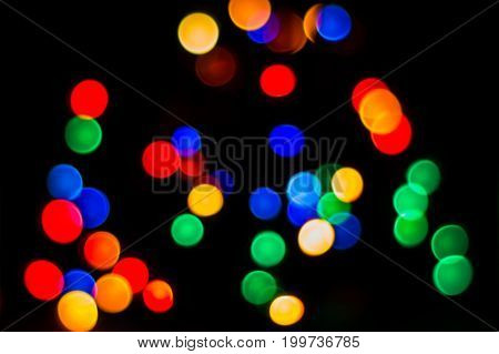 Bright and colorful circles on a dark background glowing garlands in blur