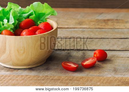 Fresh tomato and lettuce in wood bowl put on wood table. Side view close up of tomato and green oak lettuce with copy space for background. Fresh green oak lettuce and tomato prepare for cooking. Green lettuce and red tomato concept.