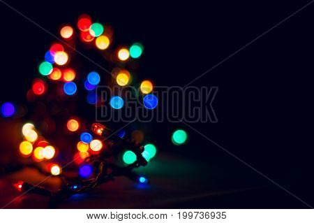 Glowing garland on a background of blurred lights on a dark background festive lighting