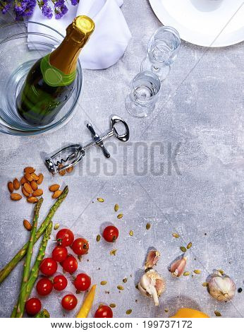 Top view of a white plate, red bright tomatoes, asparagus, cloves of garlic, almond, a bottle of champagne, silver corkscrew, snow-white napkin, little flowers, knife and fork on a grey background.