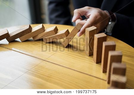 Businessman Hand Stop Dominoes Continuous Toppled Or Risk With Copyspace.