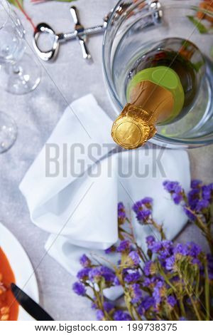 A close green bottle of champagne, little violet flowers, silvery corkscrew, glasses, a white plate with canned beans, snow-white napkin on a blurred light background.