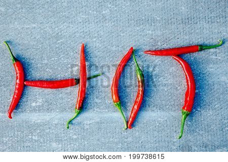Close-up of chili pepper, inscription HOT on a gray background. The concept of scalding, spices.