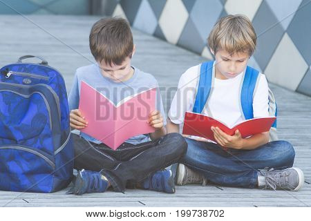 Schoolboys reading books. Children doing homework outdoors. Back to school concept.