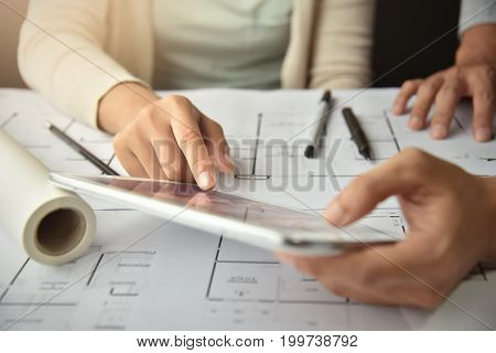 Close up Designers hands working Interior Architecture drawings with tablet on Office supplies equipment and blueprint.