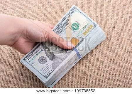 Hand Holding Banknote Bundle Of Us Dollar In Hand