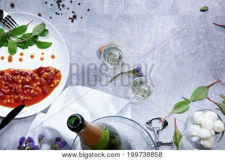 Top view of a white plate with drops of sauce and fresh green leaves, bay leaves, a half of juicy yellow lemon, little-speckled quail eggs, a jar with different seasonings on a light gray background.