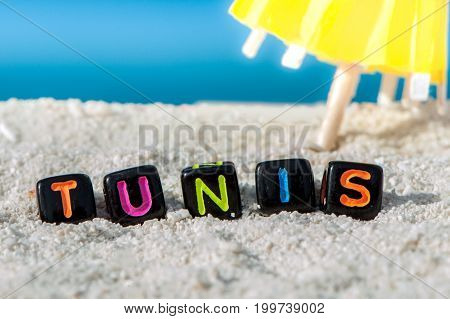 Word Tunis is made of multicolored letters on snow-white sand against the blue sea. Tourism, rest, resort, sea, sun, beach