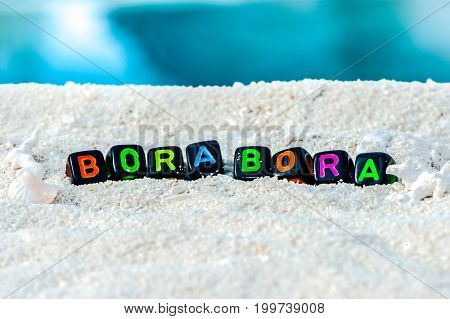 Word Bora Bora is made of multicolored letters on snow-white sand against the blue sea. Tourism, rest, resort, sea, sun, beach