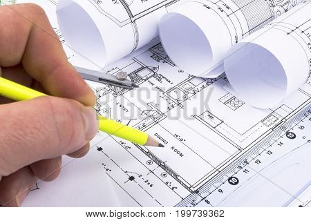 House Architectural blueprints and blueprint rolls and a drawing instruments on the worktable. Drawing compass plans. Civil Engineering Construction background.