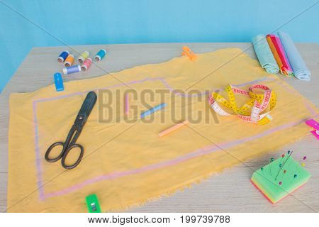 Tools for sewing for hobby set on wooden table background top view. Sewing kit. Thread needles and cloth