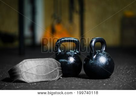 Close-up of two steel black kettlebells with a gray athletic belt on a dark blurred background, cardiovascular, strength and flexibility training, equipment used in the weight lifting sport.