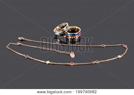 Gold rings with enamel and golden chain on dark reflective background