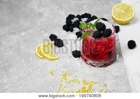 A cocktail with pieces of ice, yellow bright slices of lemon, vivid lemons, lemon peel, sappy blackberries, a glass with juice and green leaves of mint on a light gray background.