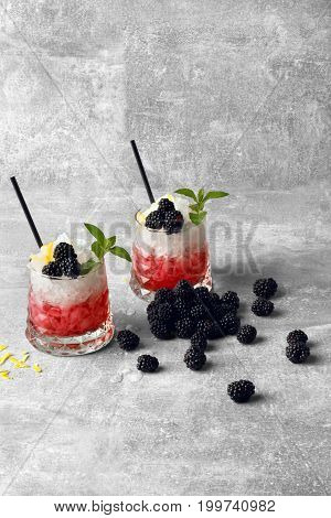 A gray table with sappy blackberries, two glasses of red fresh juice with pieces of ice and black drinking straws, yellow lemon peel on a light gray background. Refreshing drinks.