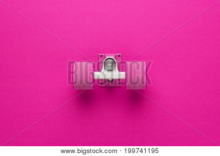 cruiser skateboard truck and wheels on deep pink with background copy space