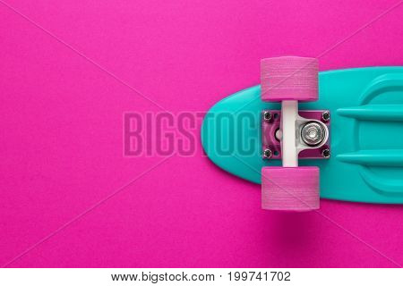 plastic mini cruiser board on deep pink with background with copy space