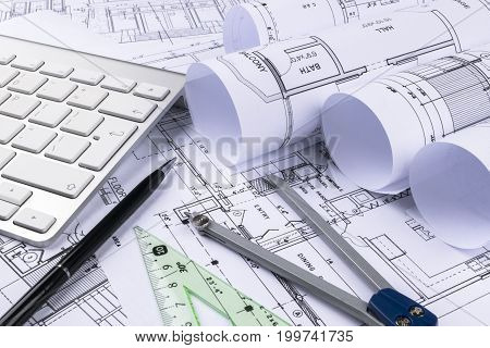 Architectural drawings of the modern house with computer keyboard. Architectural blueprints and blueprint rolls and a drawing instruments on the worktable. Drawing compass plans.