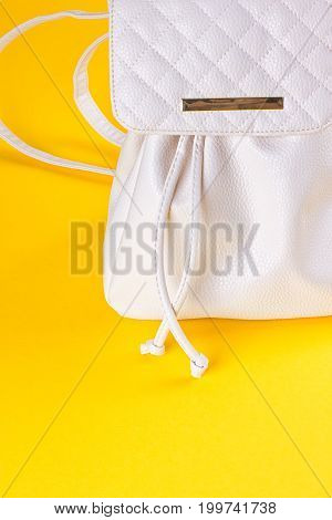 The female white leather backpack on a yellow background