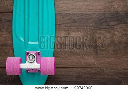 plastic mini cruiser board on wooden background with copy space