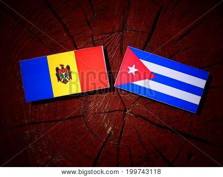 Moldovan Flag With Cuban Flag On A Tree Stump Isolated