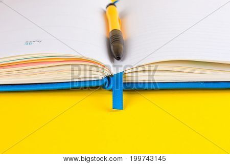 Open diary and pen on a yellow background