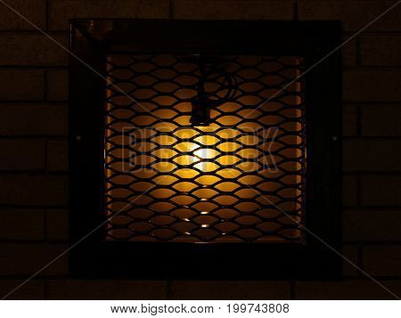 A shiny, classic, old decorative lamp in the brick wall behind metal bars in a wooden frame on a dark brown background. An elegant, antique, vintage lantern for home, pub, cafe or bar decoration.