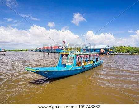 Siem Reap Cambodia - October 29 2016: A blue tourist boat docking at the bank of Tonle Sap the freshwater lake in Siem Reap Cambodia with a floating house and a floating school are at the background.