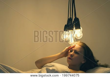 A girl lies in bed under big light bulbs can't fall asleep. Concept picture. Insomnia. Psychology.